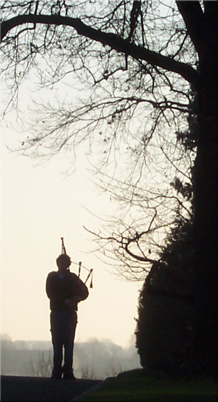 A lone piper plays his tribute at the Margraten cemetery